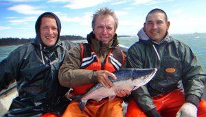Duke holding salmon on fishing boat