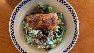Salmon filet on top of salad bed