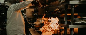 Executive Chef, Bill Ranniger, pouring oil into pan with flames