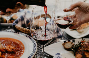 Glass of red wine being poured at dinner table