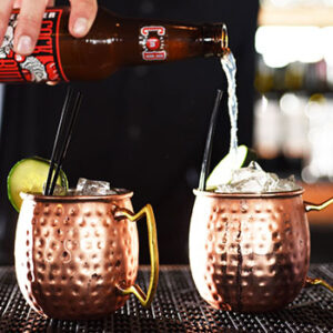 Bottle of beer pouring into one of two copper Moscow Mule mugs